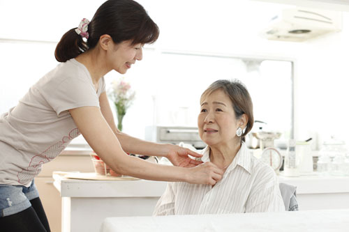 Genki HomeCare caregiver helping client with clothes